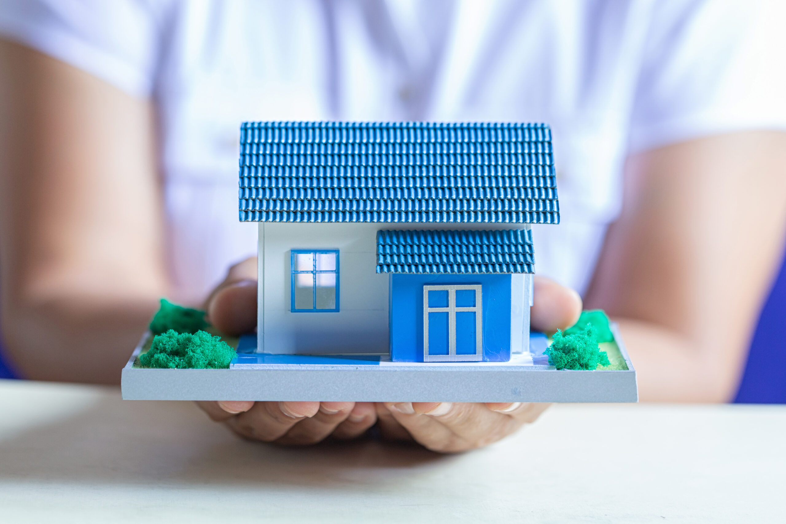 Human hands holding model of dream house